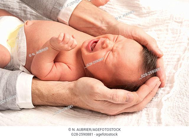 Little baby boy crying, 2 weeks old, between his father's arms and hands, trying to soothe him, and protect him;