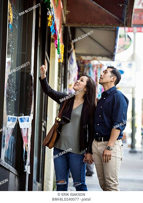 Curious Chinese couple window shopping in city