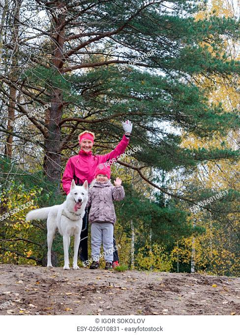 Granny with her granddaughter and a dog walk in autumn Park