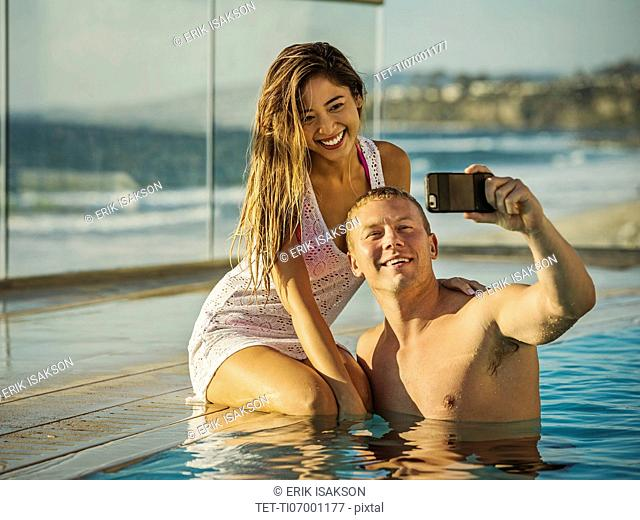 Couple taking selfie in swimming pool