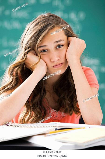 Bored Caucasian teenager studying on classroom