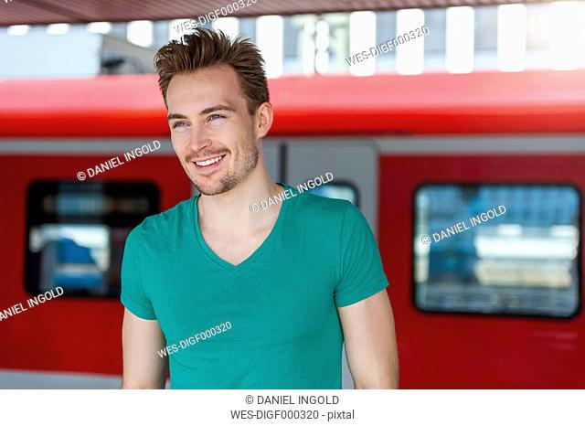 Portrait of smiling young man with stubble standing on platform