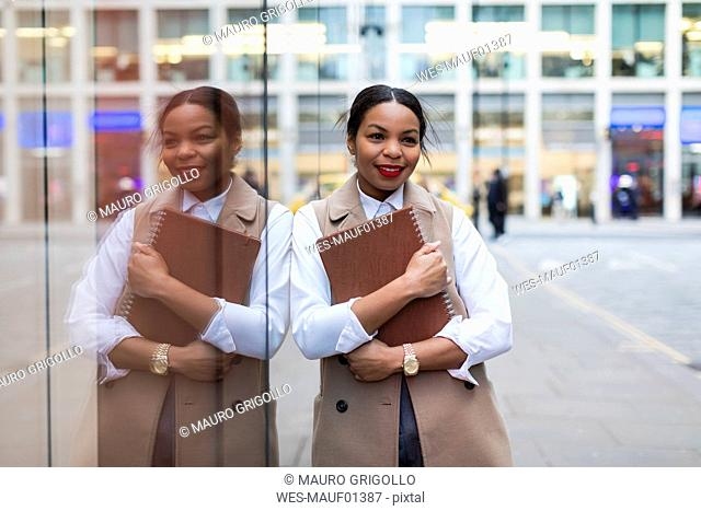 Portrait of smiling businesswoman leaning against glass pane