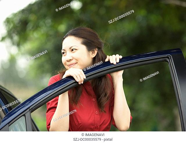 A young woman with a car door