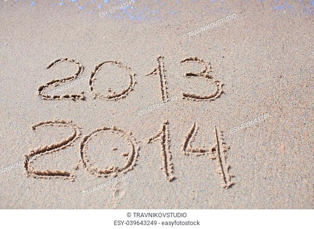 2012 and 2013 written in sand on beach