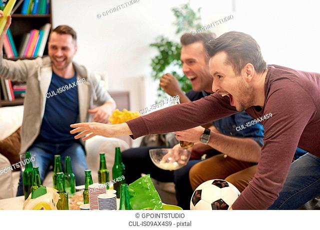 Group of men watching sporting event on television holding football celebrating