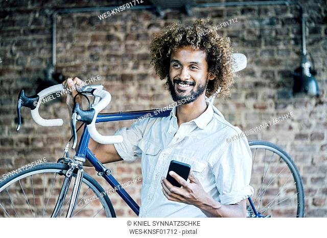 Smiling young man with bicycle and cell phone