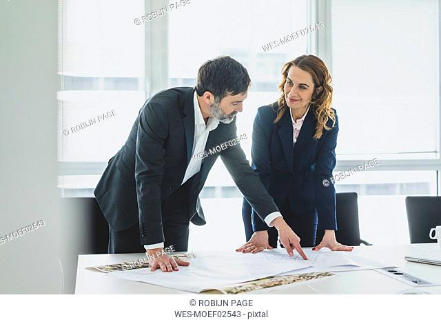 Businesswoman and businessman working on plan on desk in office