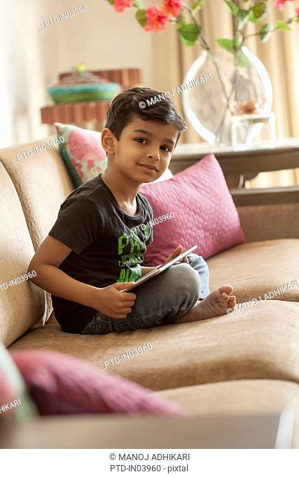 India, Little boy (4-5) sitting cross legged on sofa using digital tablet