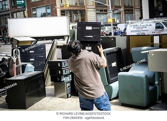 A worker moves discarded office furniture and equipment in New York