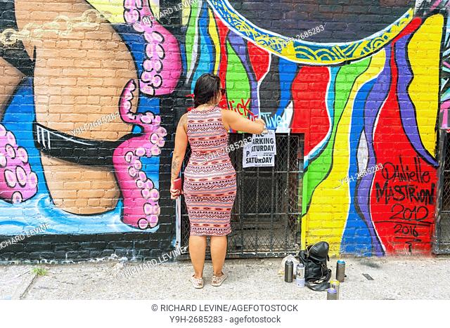 Danielle Mastrion works on her mural in Bushwick, Brooklyn in New York during the annual Bushwick Collective Block Party