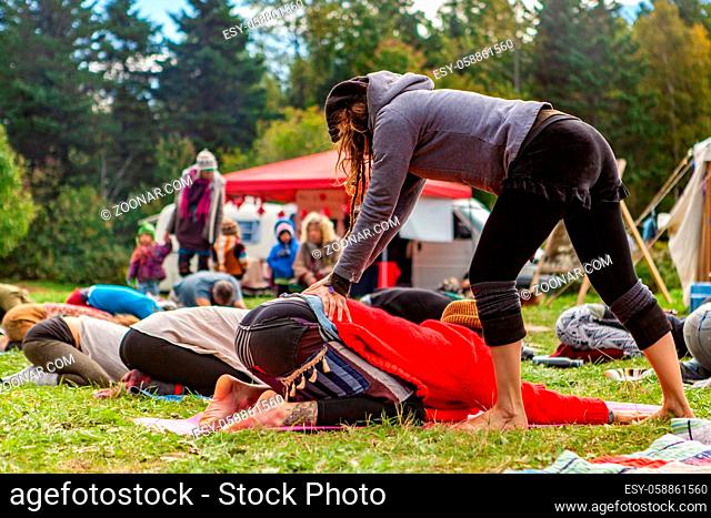 People are seen relaxing and stretching in a festival campsite, as a bohemian styled person performs lumbar back massage on one person