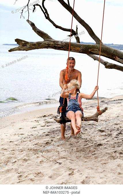 Father with swinging daughter on beach