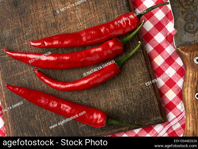 pods of red chili peppers on a brown cutting wooden board, gray table, top view