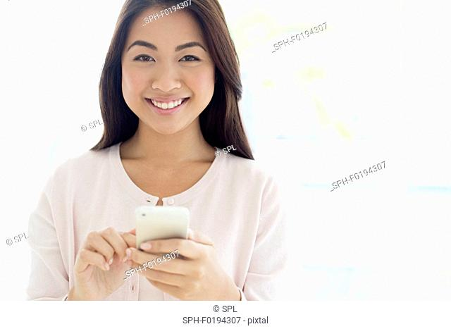 Woman using smartphone, smiling