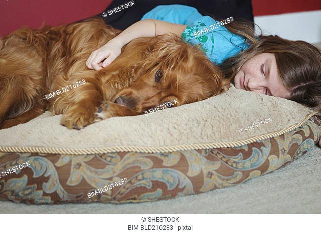 Caucasian girl cuddling dog on cushion