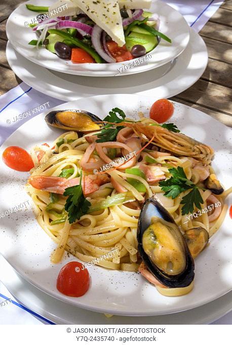 Greek Linguine di Mare and Greek salad, on the island of Paros, Greece