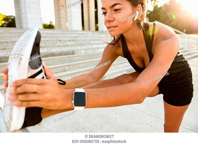 Portrait of a fitness woman in earphones doing stretching exercises on stairs outdoors