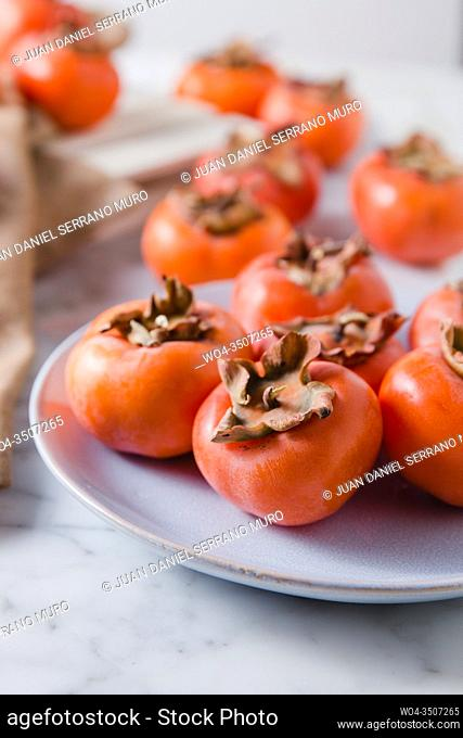 Detail close up of persimmons fresh from the garden. Natural light