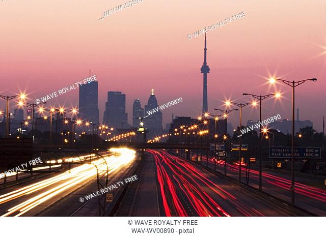 View of Toronto skyline from above Queen Elizabeth Way highway during start of rush hour traffic, Toronto, Ontario, Canada