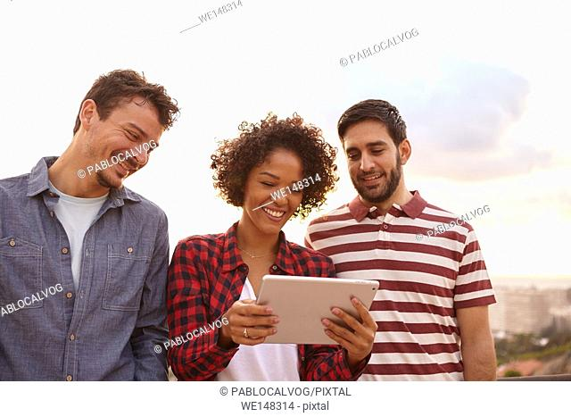 Three cute friends looking at a tablet with toothy smiles wearing casual clothing on a white background
