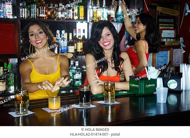 Three young waitresses serve drinks behind bar