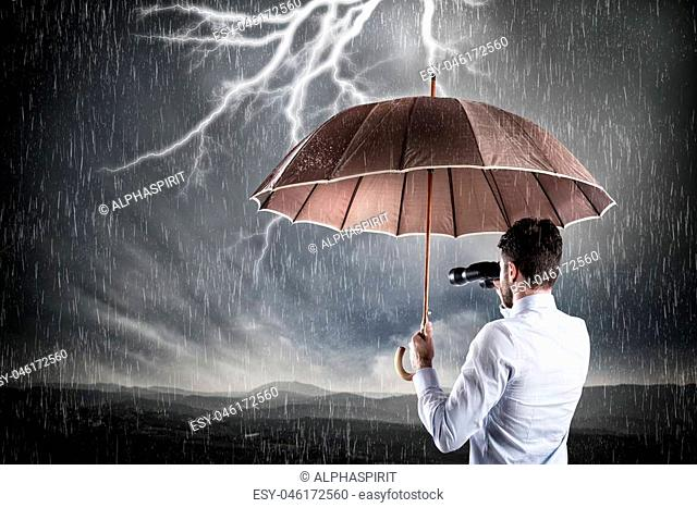 Businessman sheltered with umbrella against the storm