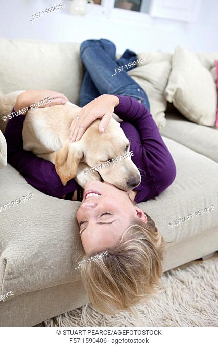 Young woman playing with her dog on the sofa