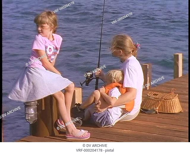 A mother and her children fish off a dock