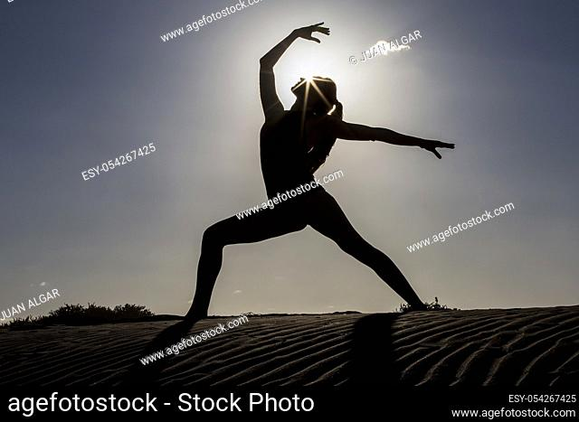 Side view of female silhouette in beautiful yoga pose standing on beach with sun back lit