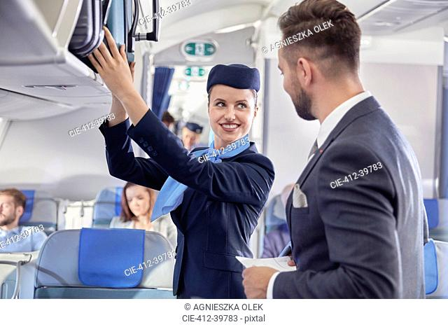 Flight attendant helping businessman with luggage on airplane