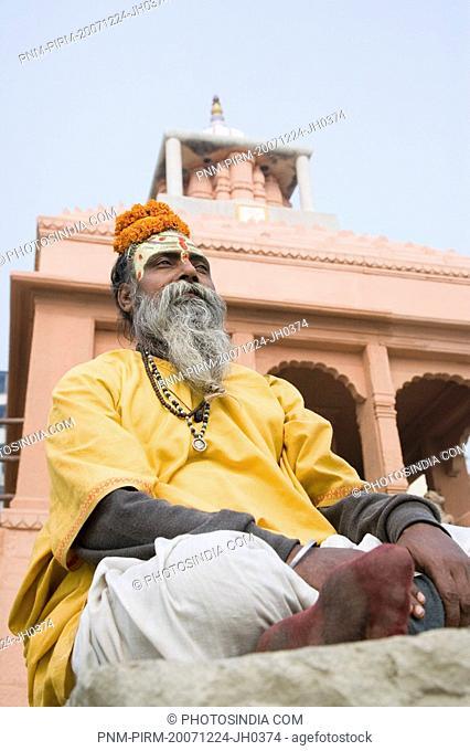 Sadhu sitting and praying in front of a temple, Varanasi, Uttar Pradesh, India