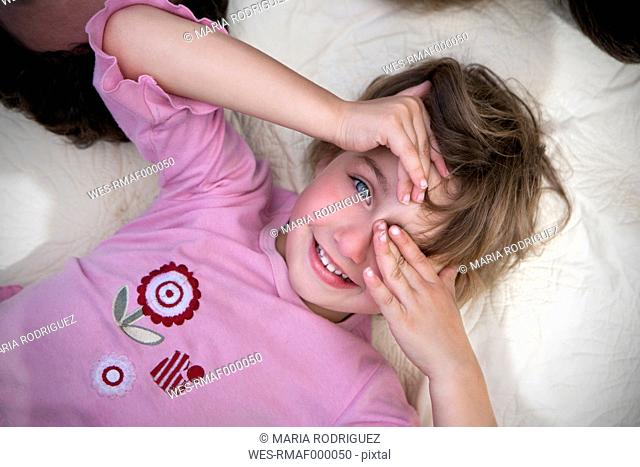 Little girl lying on blanket covering one eye with her hand