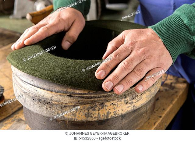 Hands shaping dry wool felt hat over edge mold, hatmaker workshop, Bad Aussee, Styria, Austria
