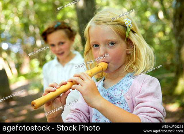 Portrait of girl playing recorder in forest