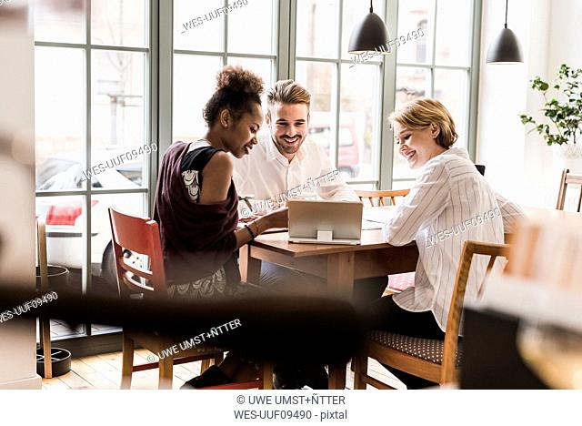 Three young people using tablet in a cafe