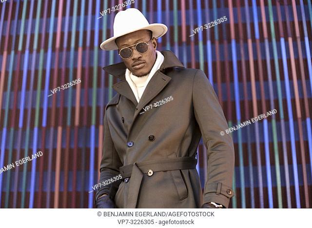 fashionable stylish blogger man wearing sunglasses and hat, in Munich, Germany