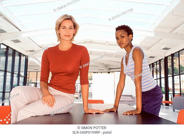 Businesswomen smiling at desk