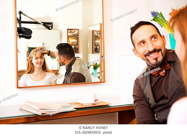Male hairdresser advising customer on hairstyle in salon