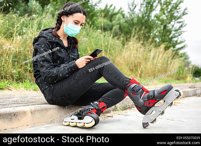 Woman in protective face mask, on roller skating pause, sitting on the street and using mobile phone during coronavirus pandemic outbreak
