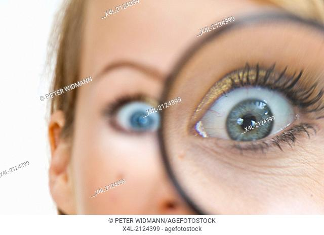 woman looking through the maginifier glass, her eye oversized (model-released)