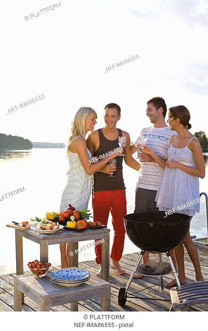 Four people standing on jetty and toasting with glasses