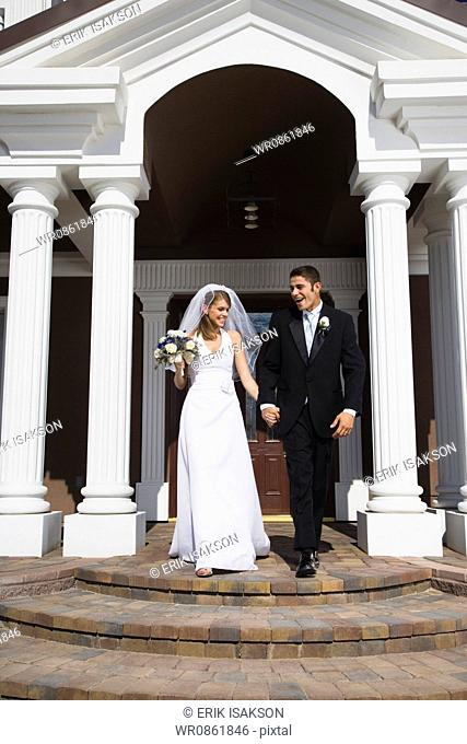 Newlywed couple walking down the steps in front of a building