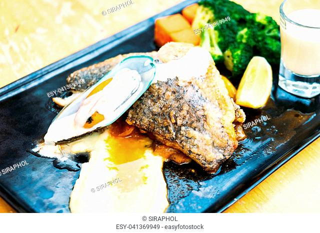 Sea bass and mussel steak in black plate