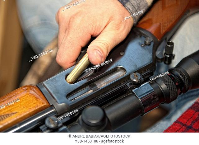 Hunter loading firearm hunting rifle with ammunition cartridge