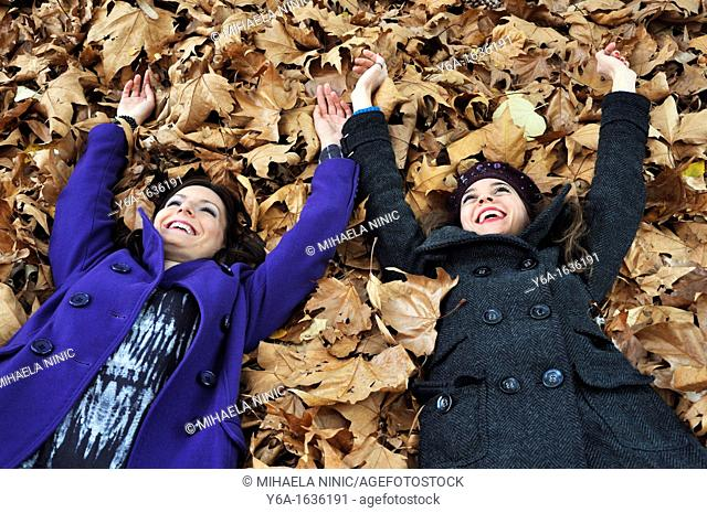 Portrait of a two young woman lying on autumn leaves from a bird's eye view laughing and having fun