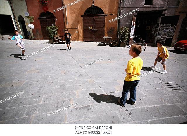 Boys Playing Soccer In Street