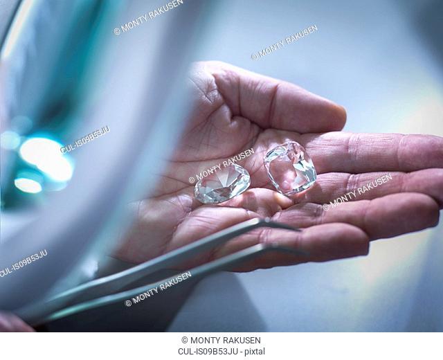 Jeweller inspecting replica diamonds in hand