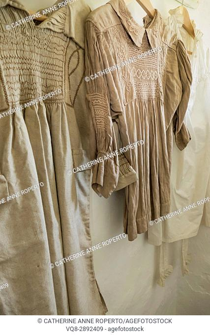 counrty smocks with traditional embroidery hung in the laundry of a Somerset cottage in England, Uk