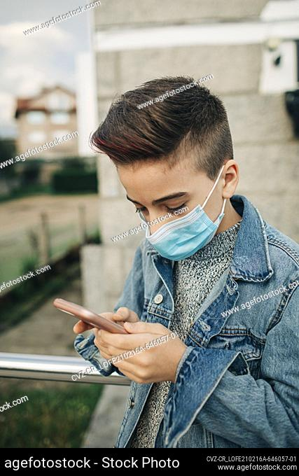Profile teen boy wearing mask and denim jacket using cellphone outdoor